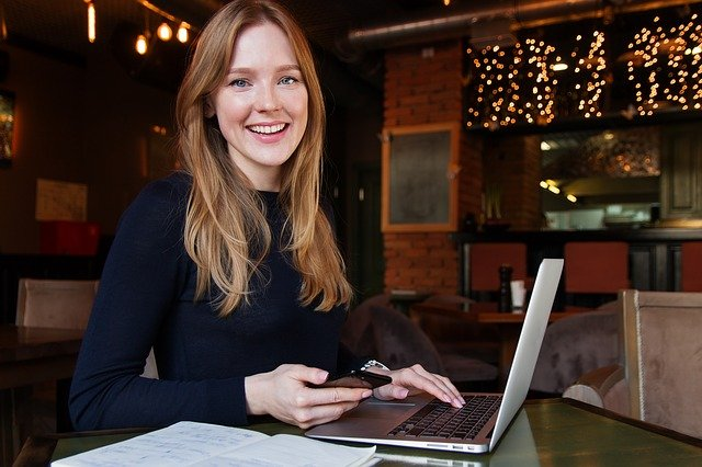 Imagem de mulher  sorrindo com celular na mão em frente a notebook