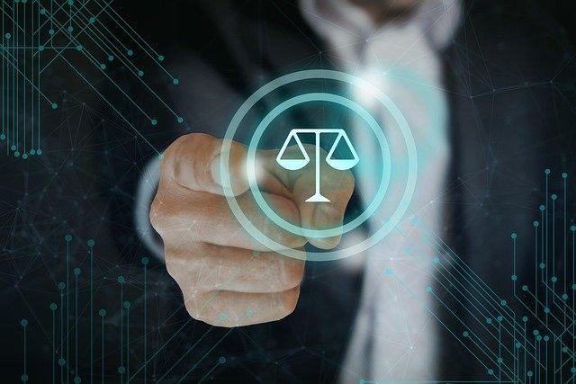 Imagem de mão masculina clicando no símbolo da justiça (uma balança)