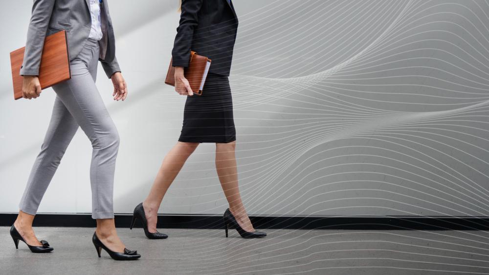 Imagem de duas mulheres de negócios, com salto alto, andando