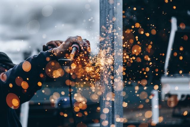 Imagem de homem utilizando ferramenta em chapa de aço